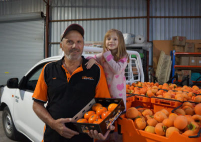 Terry and granddaughter Amelia with persimmons